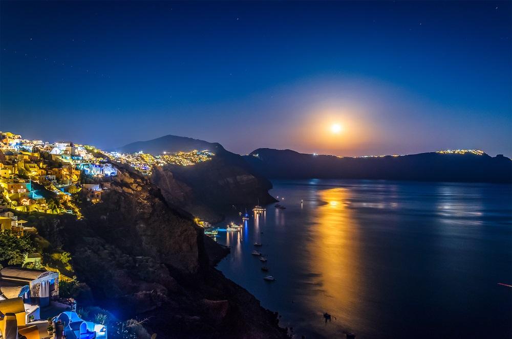 Luna Plina deasupra oraselor lumii: 16 Imagini de vis urban, care iti taie respiratia: Acolo unde orasele umane se imbina armonios cu frumusetea naturii, precum in Santorini (Grecia), luna nu face decat sa lumineze peisajul mirific