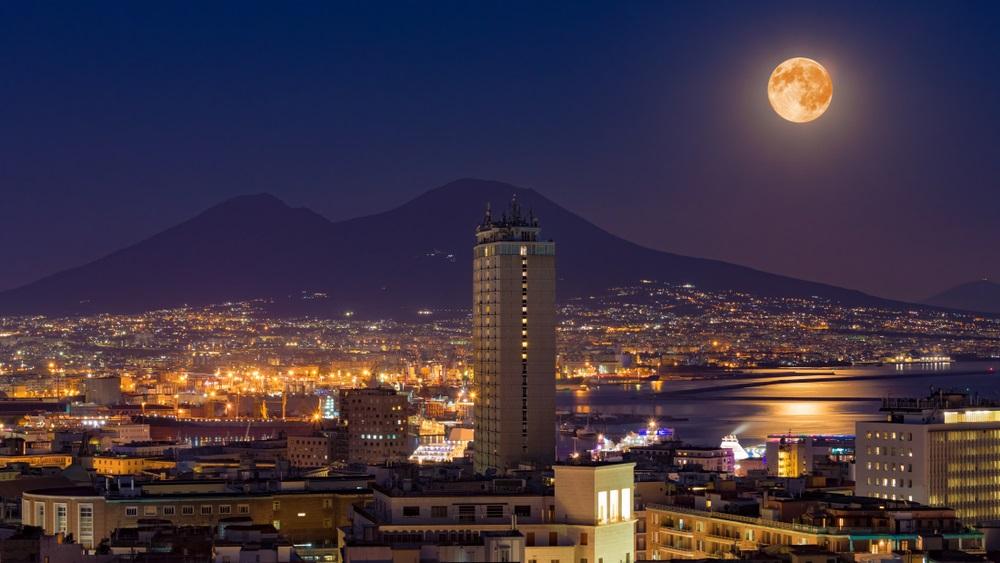 Luna Plina deasupra oraselor lumii: 16 Imagini de vis urban, care iti taie respiratia: Luna plina se reflecta duios in apele calme ale marii.  Imaginea surprinde luna plina deasupra muntelui Vezuviu si a orasului Napoli (Italia)